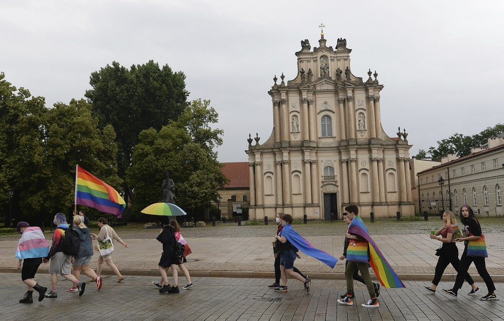 FILE - In this June 21, 2020, file photo, protesters hold a rainbow flag during an LGBT demonstration against discrimination in Warsaw, Poland. Member...