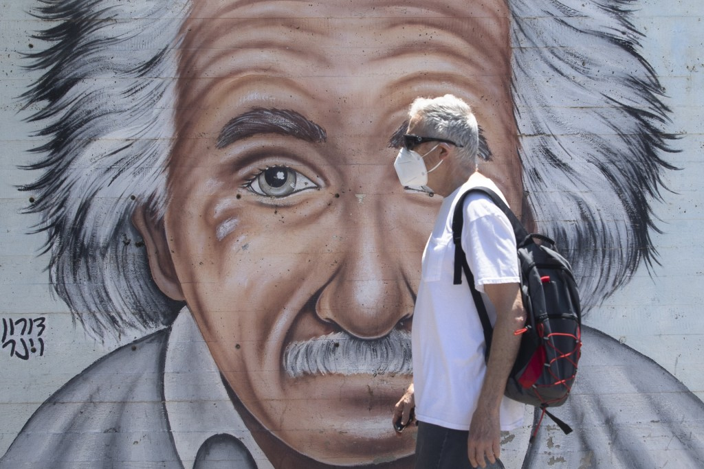 An Israeli man wearing a mask to curb the spread of the coronavirus walks past a mural showing Albert Einstein in Tel Aviv, Israel, Wednesday, July 15...
