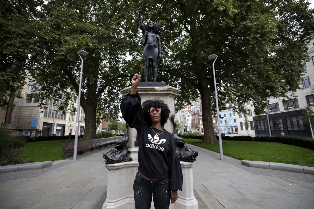 """Jen Reid poses for photographs in front of the new black resin and steel statue portraying her, entitled """"A Surge of Power (Jen Reid) 2020"""" by artist ..."""