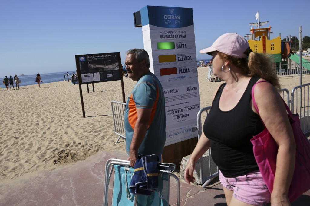 People arriving at the beach walk past a semaphore system that signals how crowded the beach is at any moment, in Oeiras, outside Lisbon, Wednesday, J...