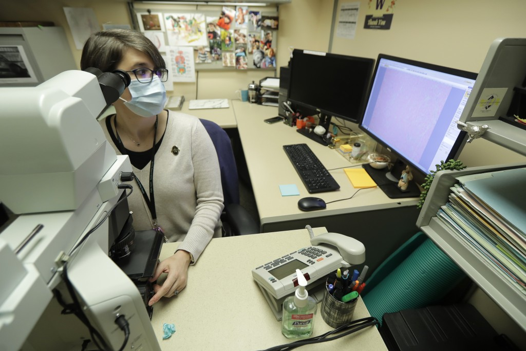 Dr. Desiree Marshall, director of Autopsy and After Death Services for University of Washington Medicine, uses a microscope to examine tissues from a ...