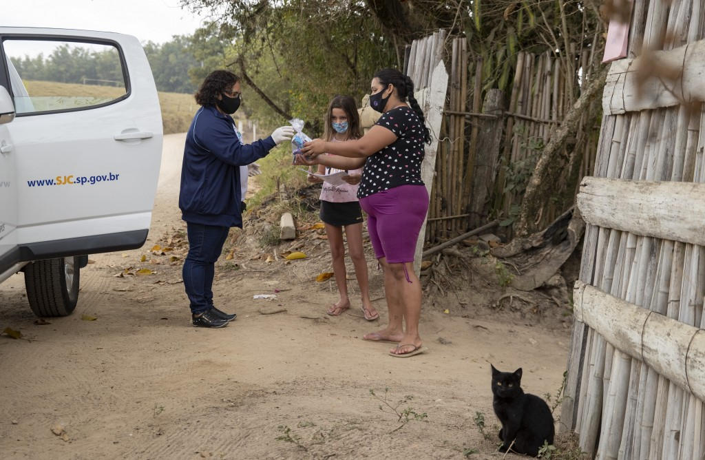 A school worker drops off schoolwork for Giovana, 9, and a bag of hygiene products to her mother Amanda Trindade outside their home in the rural area ...