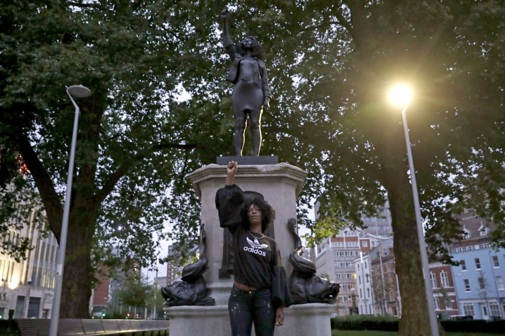 """Jen Reid poses for photographs in front of the new black resin and steel statue portraying her entitled """"A Surge of Power (Jen Reid) 2020"""" by artist M..."""