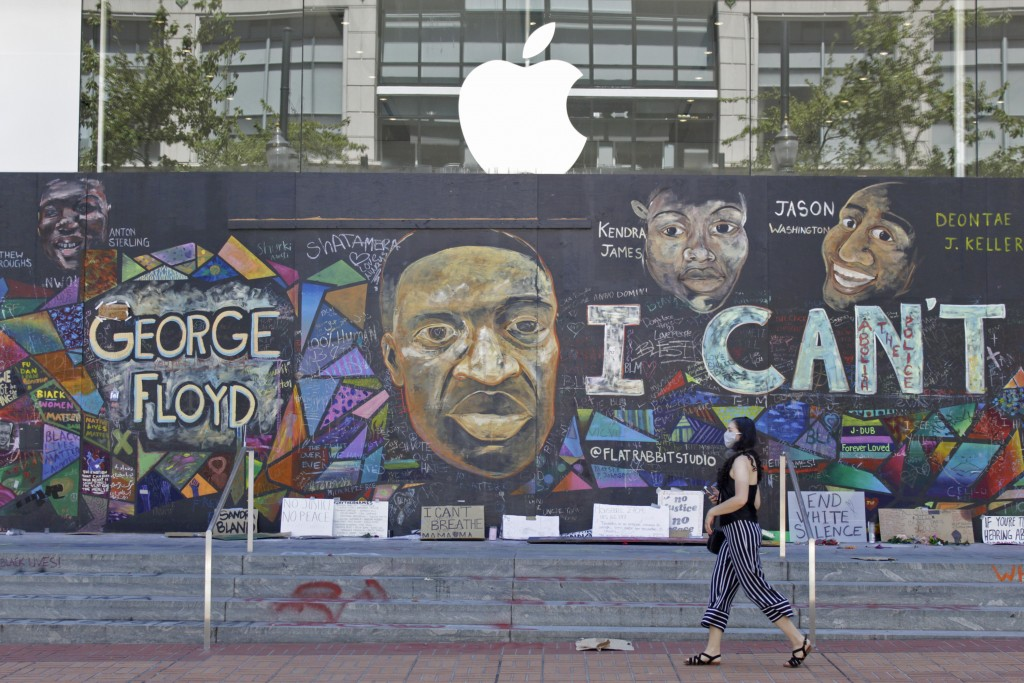 A pedestrian walks past a boarded-up Apple store that's been covered in street art in downtown Portland, Ore., Monday, July 13, 2020. While most demon...