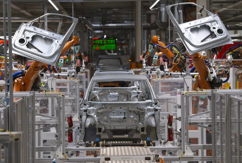 FILE- In this Tuesday, Feb. 25, 2020 file photo, robots work on an electric car ID.3 body at the assembly line during a press tour at the plant of the...