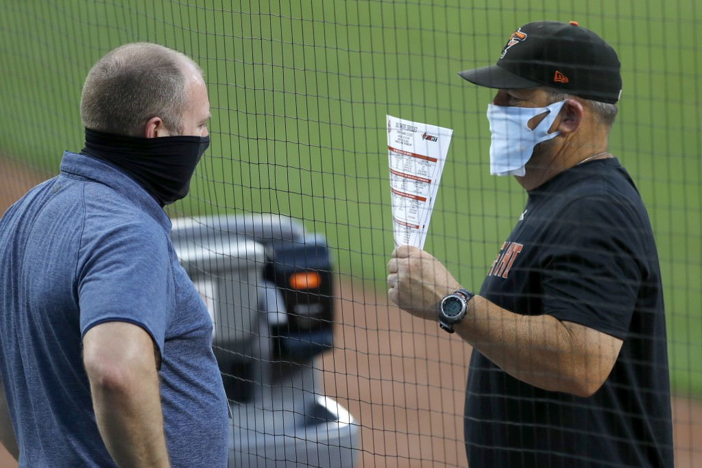 Baltimore Orioles director of baseball administration Kevin Buck, left, and field coordinator Tim Cossins wear masks to protect against COVID-19 as th...