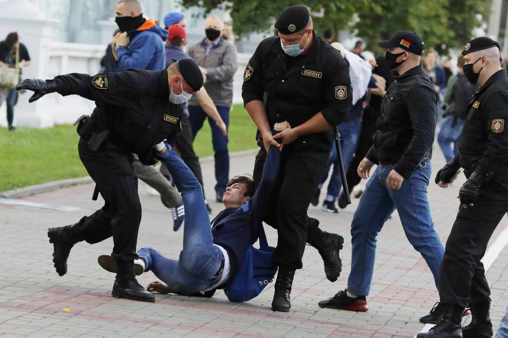 Police officers detain a protester during a rally against the removal of opposition candidates from the presidential elections in Minsk, Belarus, Tues...
