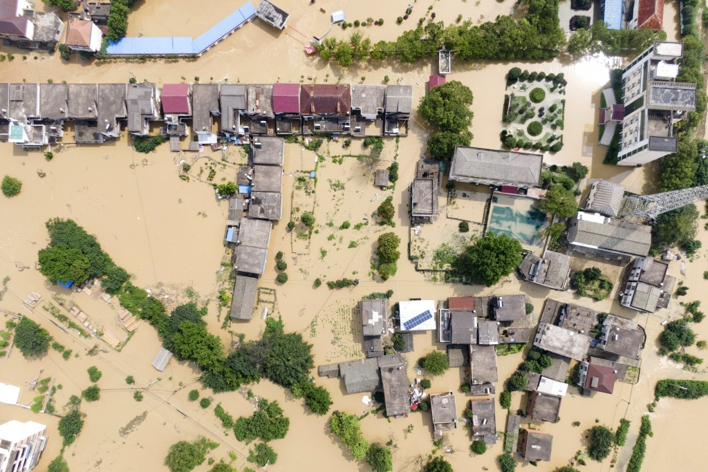 In this aerial photo released by Xinhua News Agency, a village is flooded in Sanjiao Township of the Yongxiu County in eastern China's Jiangxi Provinc...