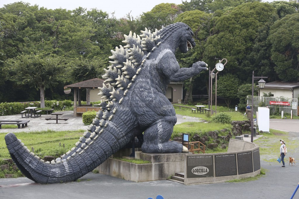 A woman wearing a face mask to protect against the spread of the new coronavirus stands near a Godzilla's slide at Kurihama flower park in Yokosuka, n...