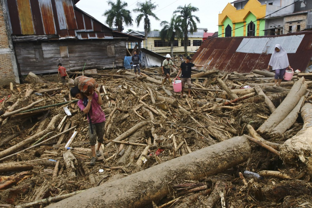 People walk on debris at an area affected by flash flood in Masamba, South Sulawesi province, Indonesia, Wednesday, July 15, 2020. Rescuers on Wednesd...