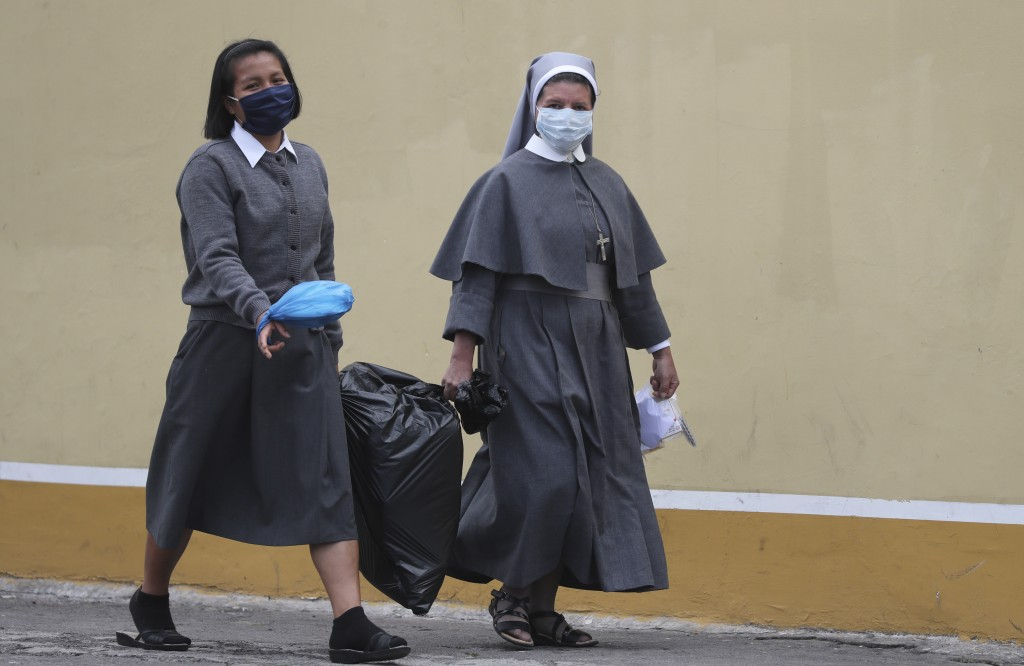 Nuns wearing masks to curb the spread of the new coronavirus, walk in the streets of Quito, Ecuador, Tuesday, Julio 14, 2020. (Foto AP/Dolores Ochoa)