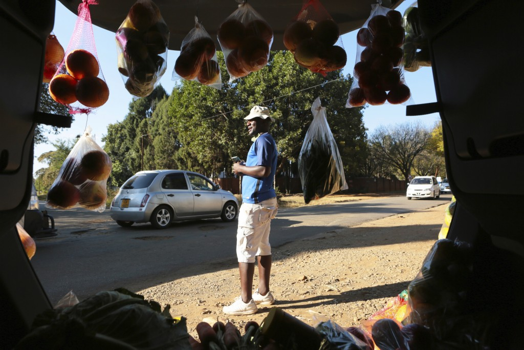 A man displays fruits and vegetables inside his car trunk while selling them by the side of a busy road in Harare, Zimbabwe, Tuesday, July 7, 2020. Ca...