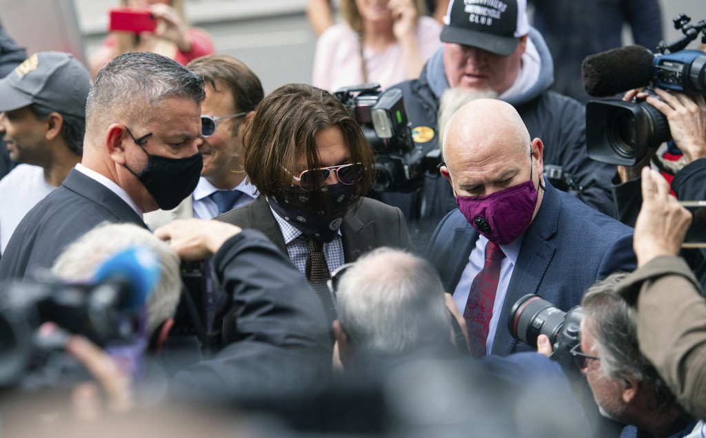 Actor Johnny Depp, centre, arrives at the High Court to give evidence in his libel case, in London, Wednesday July 15, 2020. Depp is suing News Group ...