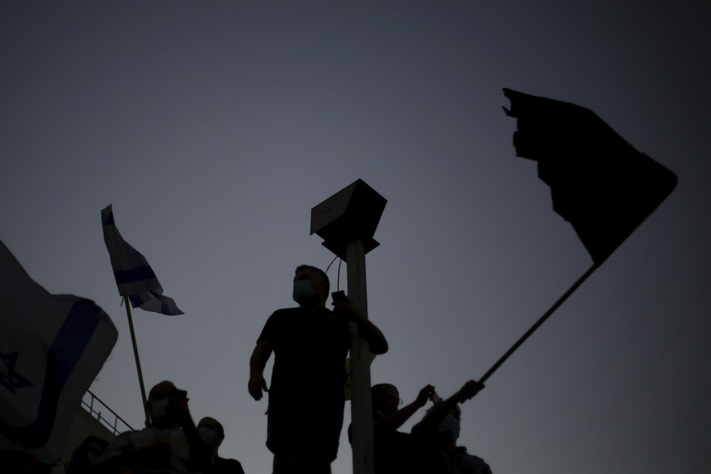 Protesters  wave flags outside of the Prime Minister's residence in Jerusalem, Tuesday, July 14, 2020. Thousands of Israelis on Tuesday demonstrated o...