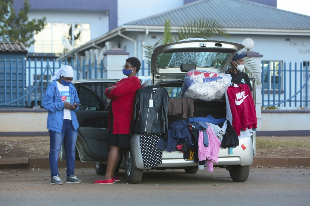 People sell clothes displayed on their car by the side of a busy road in Harare, Zimbabwe, Tuesday, June, 23, 2020. Cars have become mobile markets in...