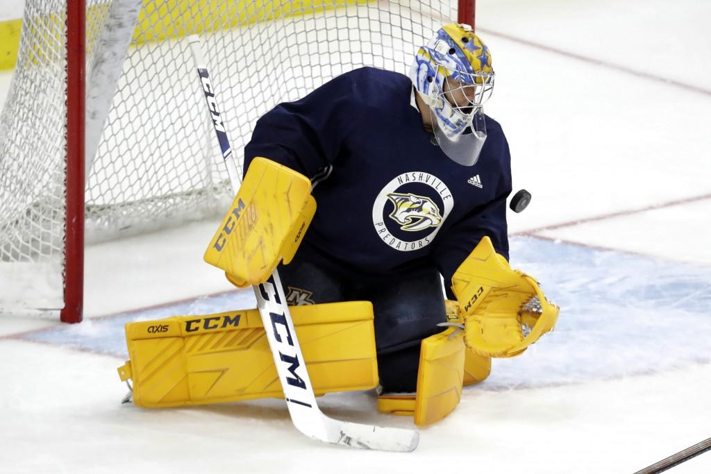 Nashville Predators goaltender Juuse Saros, of Finland, blocks a shot during NHL hockey training camp, Tuesday, July 14, 2020, in Nashville, Tenn. (AP...