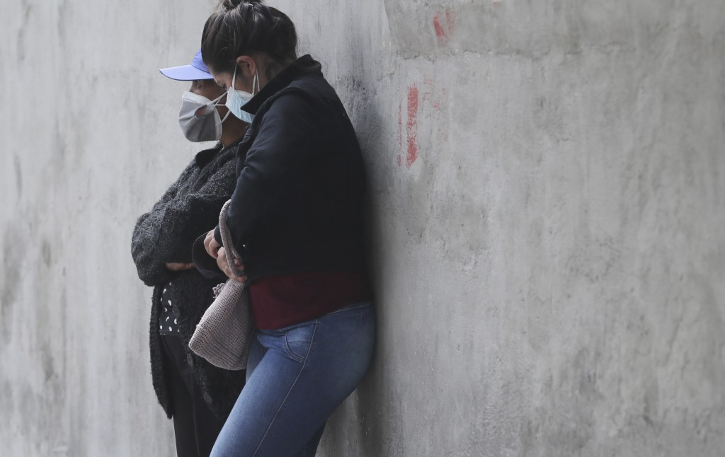Women wait for the remains of a relative who died from COVID-19 complications, outside the Pablo Arturo Suarez Hospital in Quito, Ecuador, Tuesday, Ju...