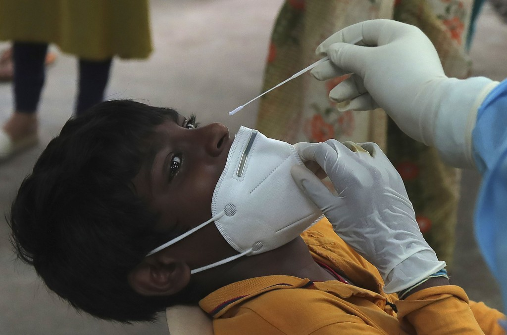A boy gets his nasal swab sample taken to test for the coronavirus at a government health center in Hyderabad, India, Wednesday, July 15, 2020. As Ind...
