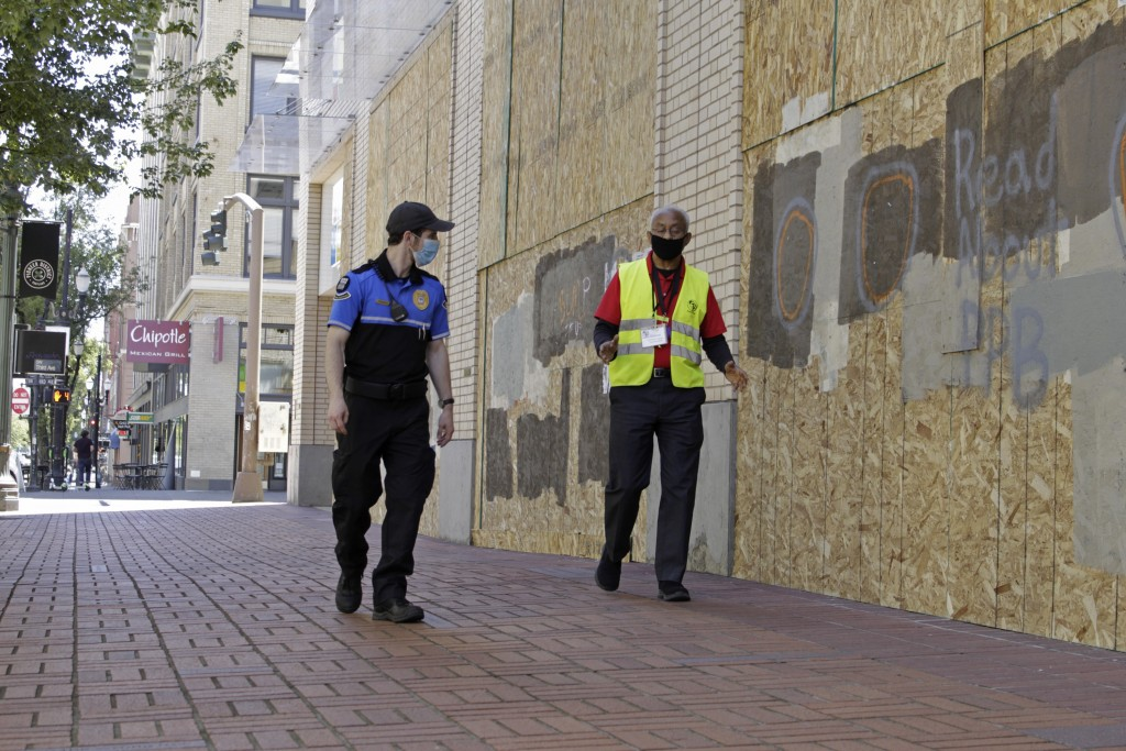 Two security officers walk in downtown Portland, Ore., Monday, July 13, 2020, alongside an entire block of shop windows that have been boarded up foll...