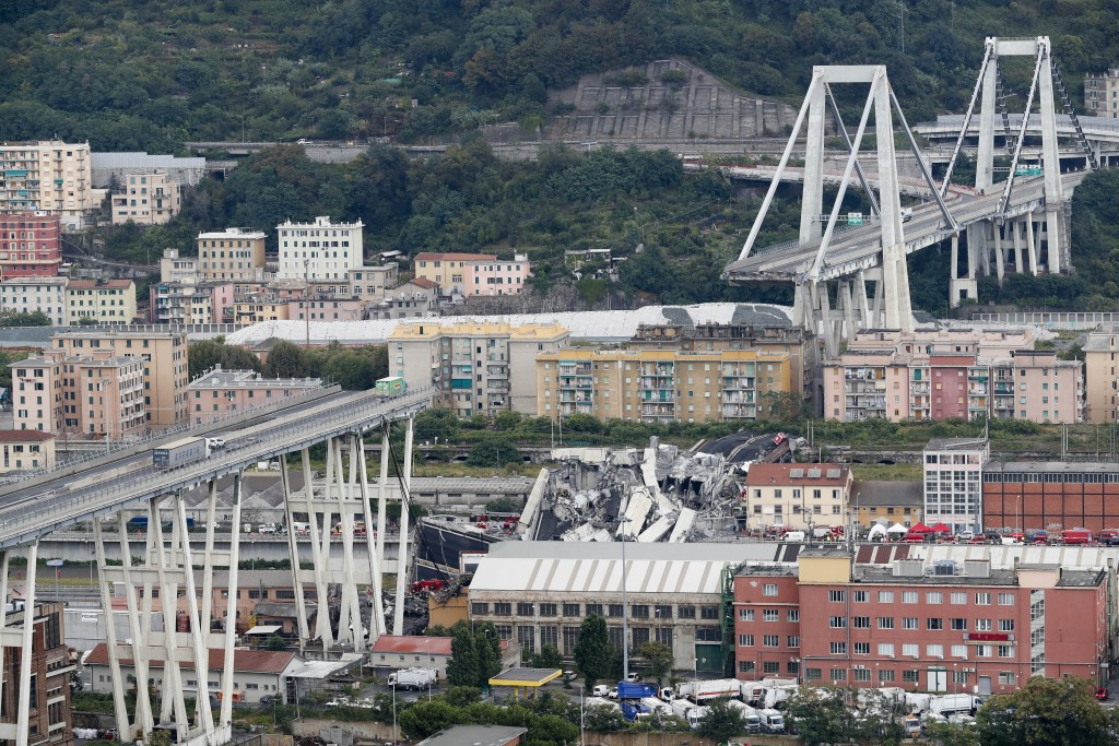 FILE - In this Tuesday, Aug. 14, 2018 file photo, cars are blocked on the Morandi highway bridge after a section of it collapsed, in Genoa, northern I...