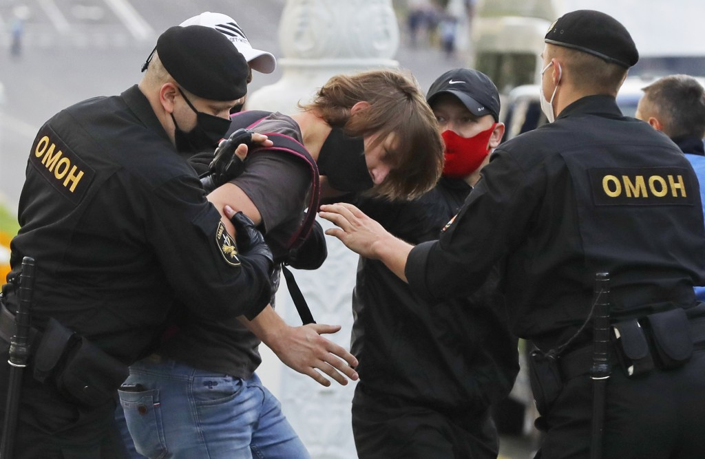 Police officers detain a protester during a protest rally against the removal of opposition candidates from the presidential elections in Minsk, Belar...