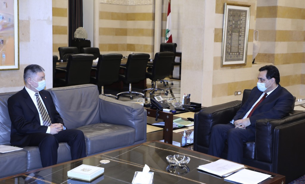 In this photo released by Lebanon's official government photographer Dalati Nohra, Lebanese prime minister Hassan Diab, right, meets with China's amba...