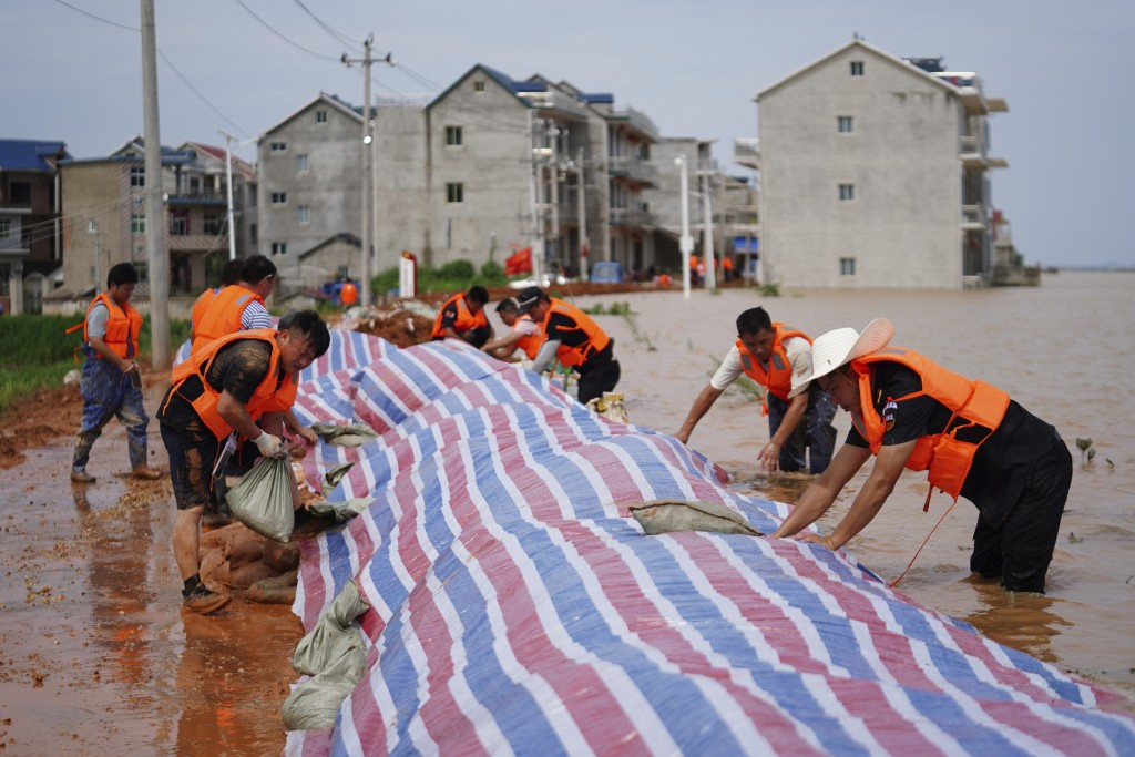 In this photo released by Xinhua News Agency, workers build a dyke to stop flood waters at Jiangjialing village of Poyang County in eastern China's Ji...