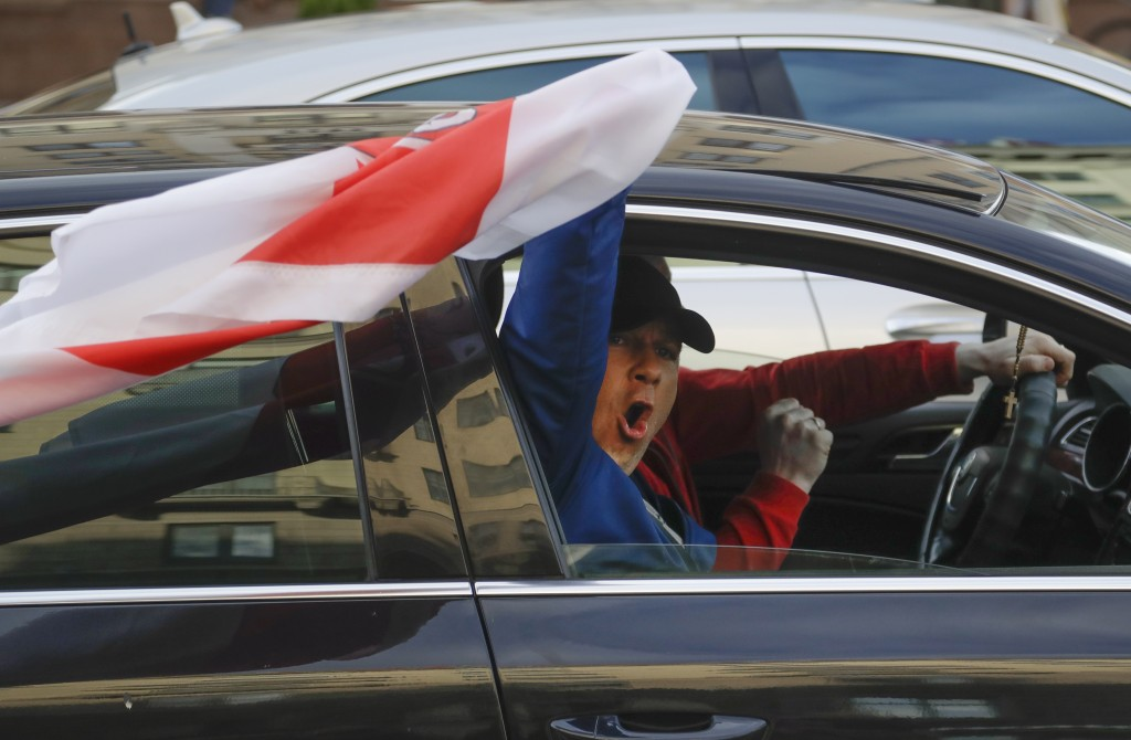 A man waves a flag from a window of a car during a protest rally against the removal of opposition candidates from the presidential elections in Minsk...