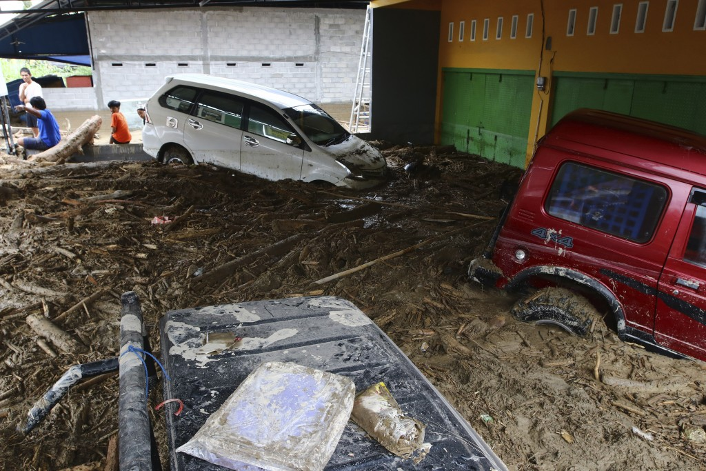 Cars are stuck in mud at an area affected by flash flood in Masamba, South Sulawesi province, Indonesia, Wednesday, July 15, 2020. Rescuers on Wednesd...