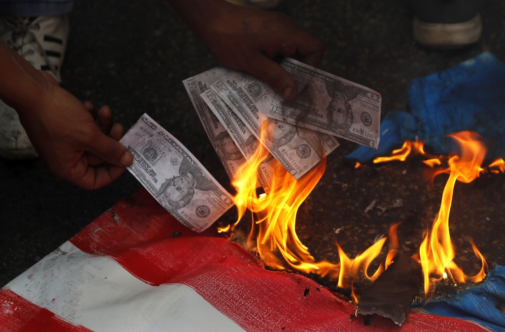 FILE - In this July 10, file, photo, a supporter of a communist group burns representation of U.S. currency, during a protest against U.S. interferenc...