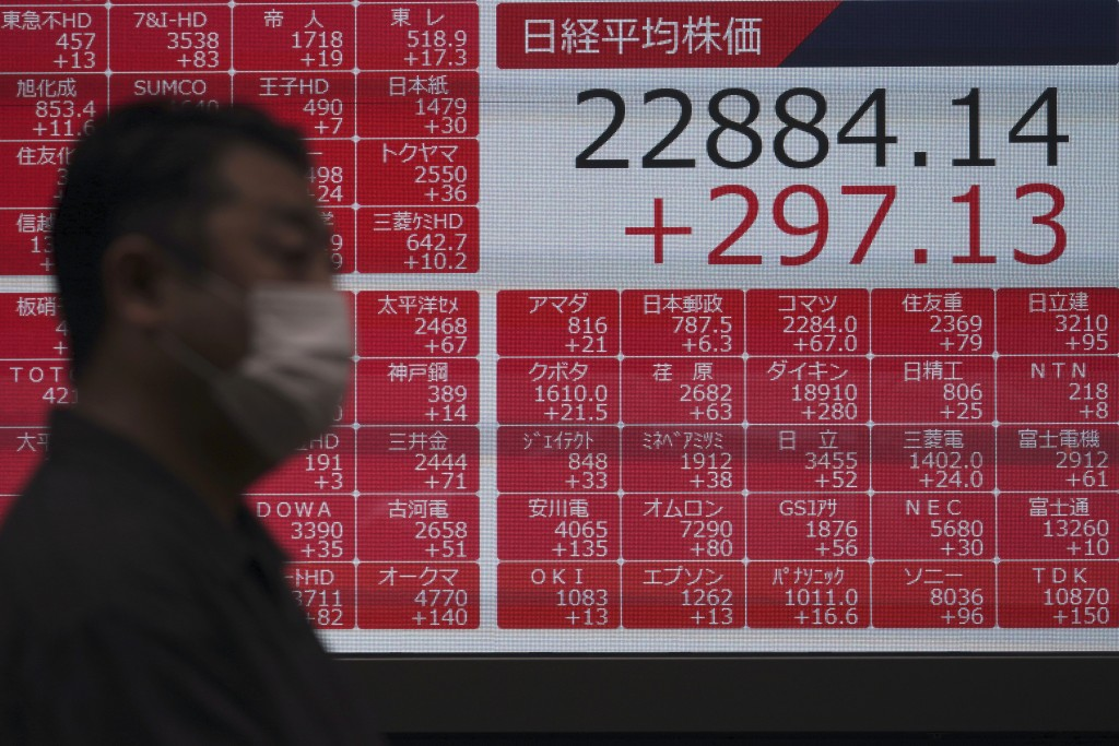 A man walks past an electronic stock board showing Japan's Nikkei 225 index at a securities firm in Tokyo Wednesday, July 15, 2020. Shares were mostly...
