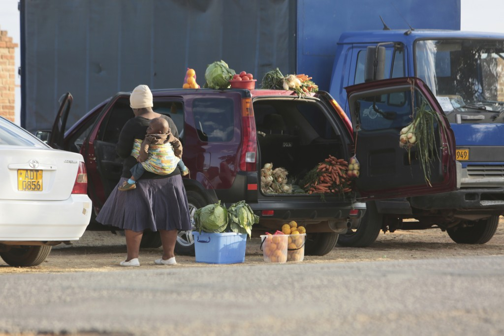 People sell various goods by the side of a busy road in Harare, Zimbabwe, Tuesday, June, 23, 2020. Cars have become mobile markets in Zimbabwe where e...