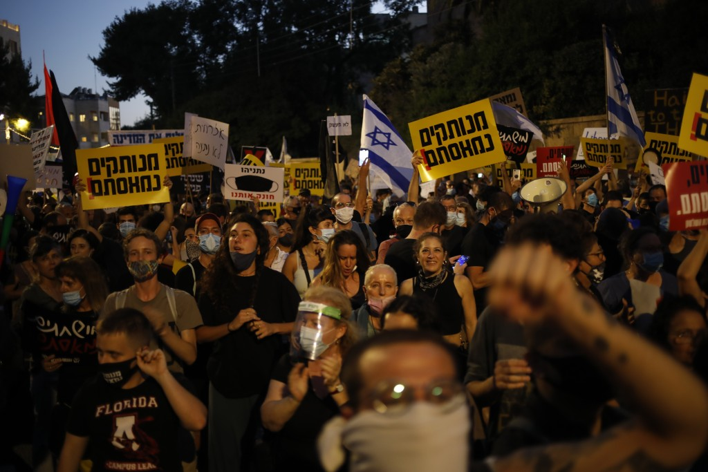 Demonstrators, defying orders to maintain social distancing requirements, chant slogans and blow horns outside the Prime Minister's residence in Jerus...
