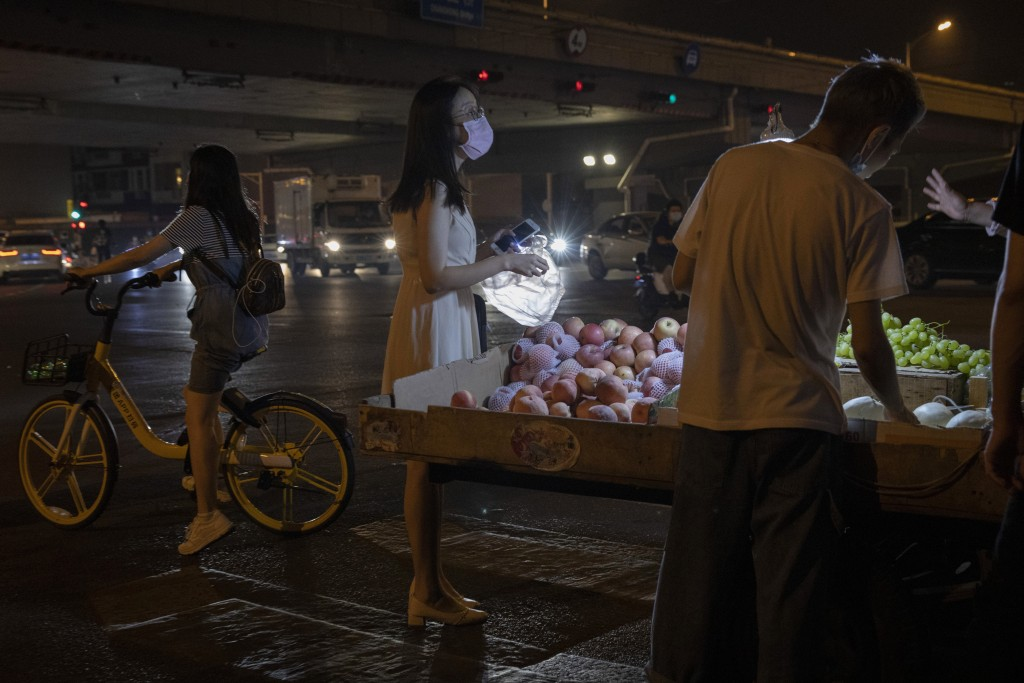 A woman wearing a face mask to curb the spread of the coronavirus buys fruit from a street vendor in Beijing, China, Tuesday, July 14, 2020. Small bus...