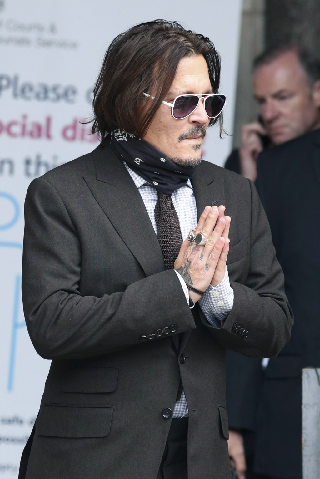 Actor Johnny Depp gestures as he arrives at the High Court to give evidence in his libel case, in London, Wednesday July 15, 2020. Depp is suing News ...