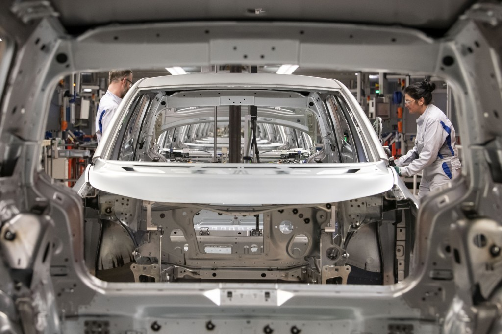 FILE- In this Tuesday, Feb. 25, 2020 file photo, workers complete an electric car ID.3 body at the assembly line during a press tour at the plant of t...