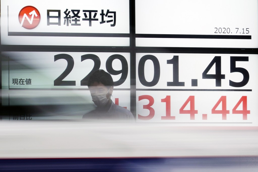 A man stands in front of an electronic stock board showing Japan's Nikkei 225 index at a securities firm as a car passes by in Tokyo Wednesday, July 1...