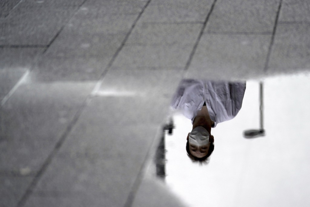 A man wearing a face mask to help curb the spread of the new coronavirus is reflected on puddle on a street after the rain Wednesday, July 15, 2020, i...