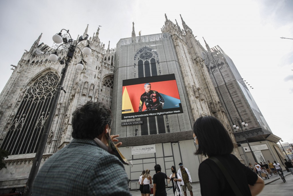 Pedestrians pass by a screen on the Duomo cathedral, showing a Moschino model during the Milan Digital Fashion Week, in Milan, Italy, Tuesday, July 14...