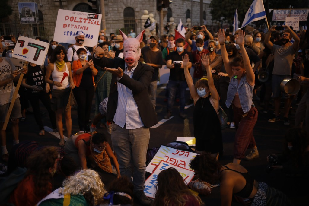 Protesters, defying orders to maintain social distancing requirements, chant slogans outside of the Prime Minister's residence in Jerusalem, Tuesday, ...