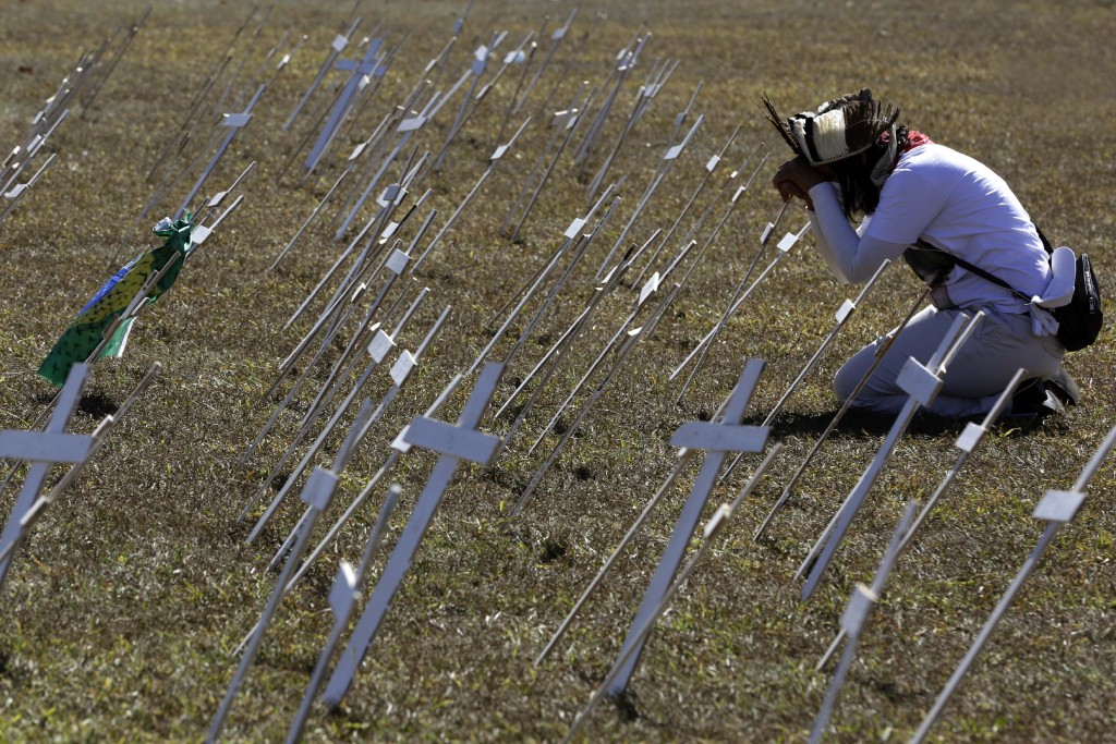 A demonstrator kneels before rows of crosses representing the thousands of deaths due to the new coronavirus, during a protest demanding President Jai...