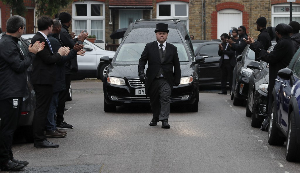 In this photo taken on Thursday, June 11, 2020, grass roots soccer referees form a guard of honour and clap as the hearse carrying the coffin of  Jerm...