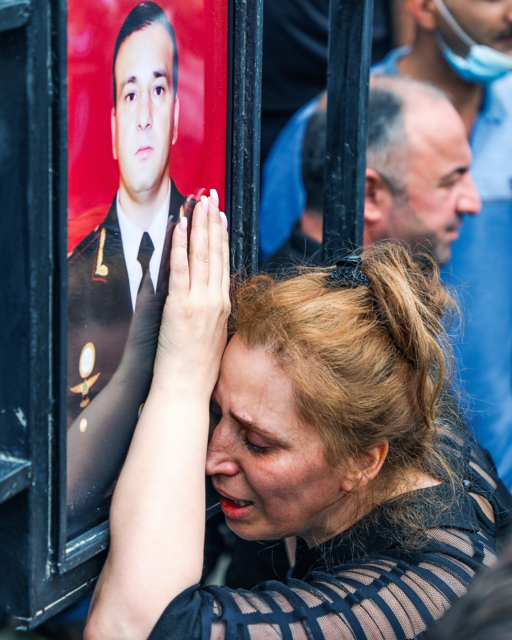 Widow of Maj. Gen. Polad Hashimov, who was killed in fighting Tuesday along with five other servicemen, mourns at his portrait during the funeral cere...