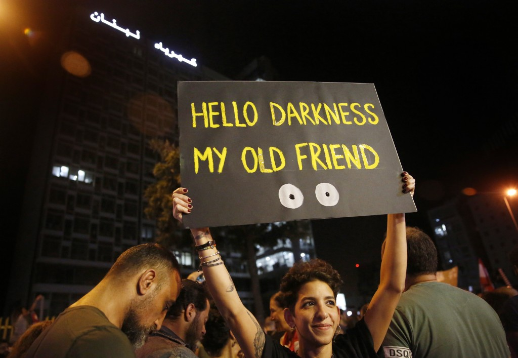 FILE - In this Nov. 7, 2019, file, photo, an anti-government protester holds up a placard in front the Lebanese electricity company headquarters, duri...