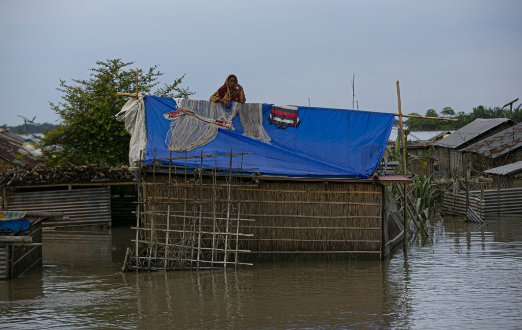 A flood affected Indian woman stands on the roof of her partially submerged house along river Brahmaputra in Morigaon district, Assam, India, Thursday...