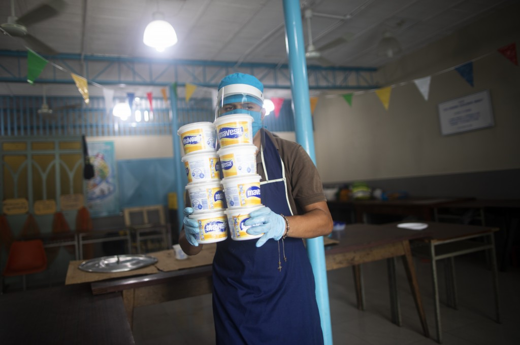A volunteer wearing protective gear as a precaution against the new coronavirus carries containers of soup to be given away to residents at a soup kit...