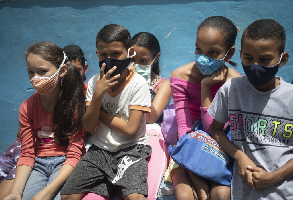 Children wearing protective face masks as a precaution against the new coronavirus wait outside a soup kitchen to receive a pack-and-go lunch in the P...