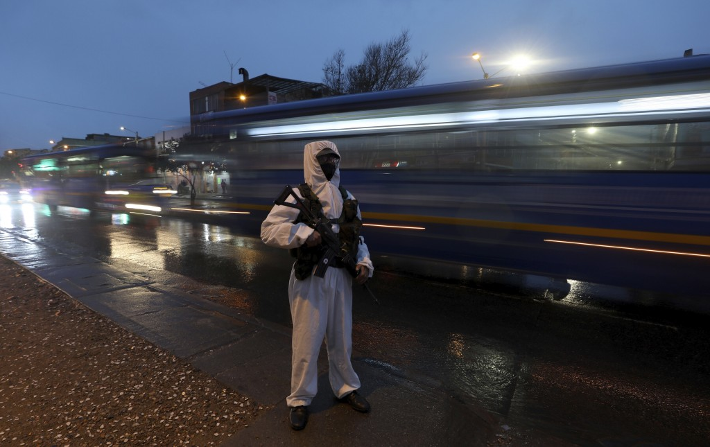 A soldier in protective gear amid the new coronavirus pandemic patrols the streets of Usme, an area with a high number of COVID-19 cases in Bogota, Co...