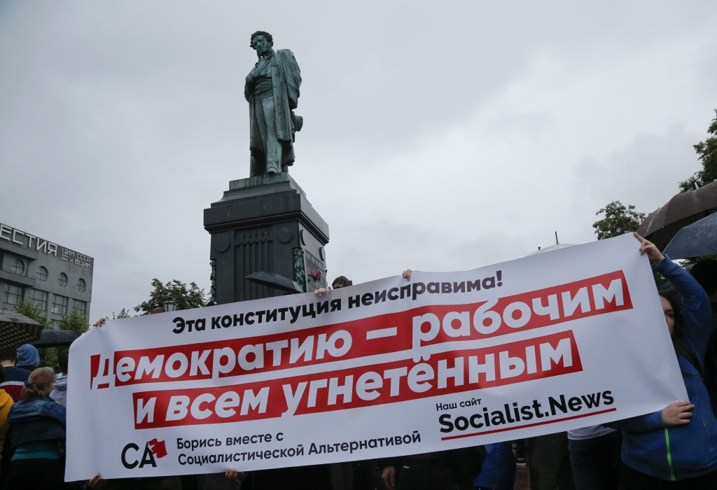 People hold a banner as they attend a rally to collect signatures to cancel the results of voting on amendments to the Constitution in Pushkin Square,...