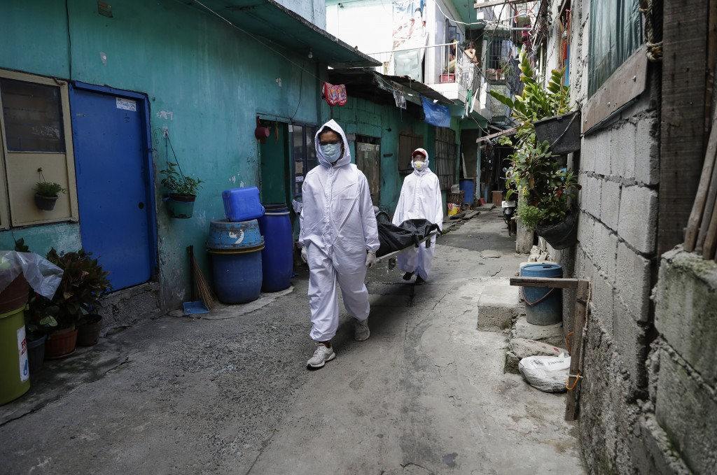 Funeral home workers in protective suits carry a body during the start of a lockdown due to a rise in COVID cases in the city of Navotas, Manila, Phil...